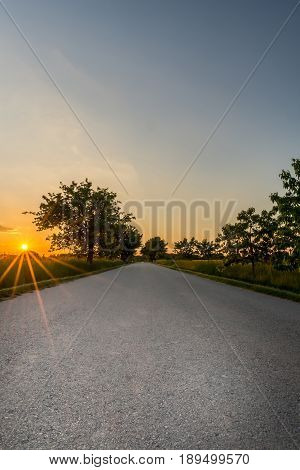 Sunset With Long Orange Beams Over The Road