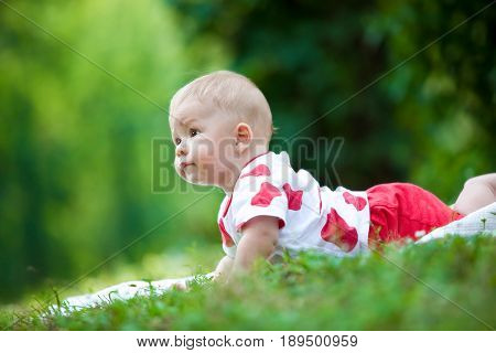 One-year-old baby lies on a plaid in the middle of a green grass and looks closely into the distance