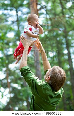 Dad highly throws his son in the middle of a green forest. Kid screwed up his eyes from the stare