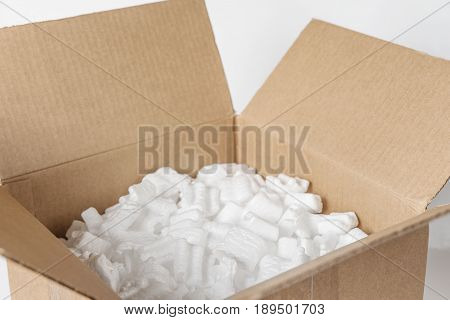 Opened cardboard box filled with polystyrene foam chips on a white background close-up