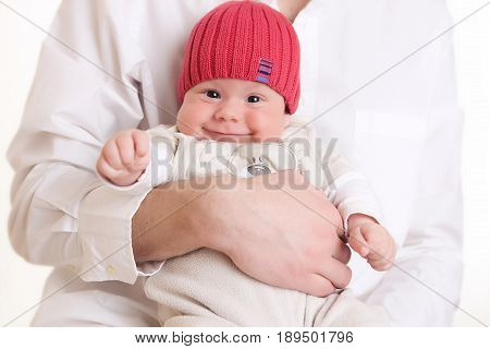 baby in the red hat is incredibly smiling while his father is holding him