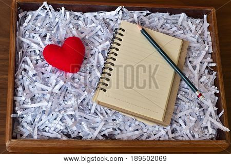 Blank notebook and pencil put on shredded paper with red heart in wooden box