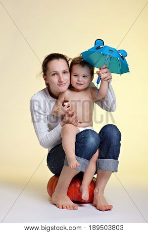 The child is holding a funny blue umbrella with ears sitting on the lap of his mother