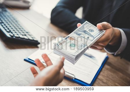 Businessman giving money US dollars to his partner while making contract - loan bribery and corruption concepts