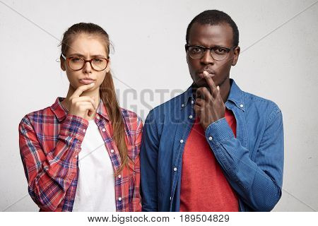 International Friendship Concept. Afro American Man And European Female Looking Suspiciously Holding