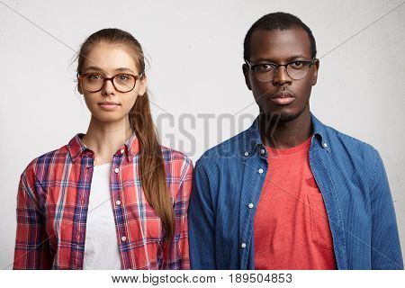 Horizontal Portrait Of Two Mixed Race People Posing Against White Background Looking Into Camera. Yo