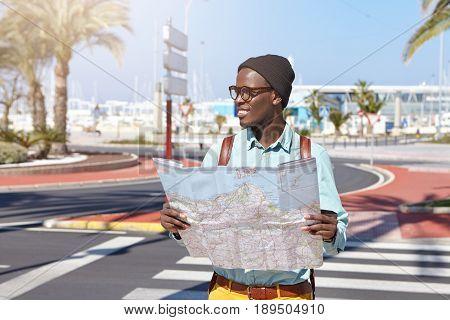 Headshot Of Afro American Male Traveler Wearing Stylish Black Cap, Shirt And Glasses Holding City Gu
