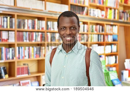 Portrait Of Dark-skinned Male Student Holding Rucksack Standing In Library Choosing Interesting Book