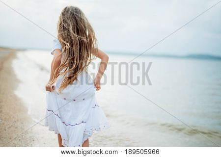 Blurred image Copy space Background Long-haired girl in white clothes runs along seashore near sea in early morning at dawn. Selective focus. High key