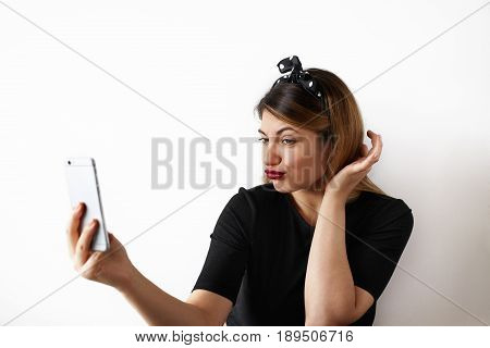 portrait of attractive girl making a duck face posing for selfie holding cell phone. Pretty girl with red lips going crazy and having fun and grimacing posing in studio on white wall background