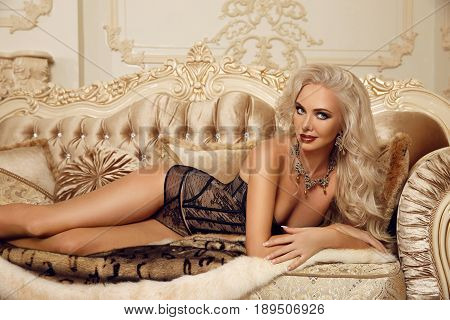 Beautiful alluring blond woman in sexy lingerie lying on royal sofa in luxury modern interior. Beauty glamour fashion style photo portrait.