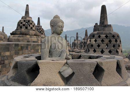 Borobudur Temple in Java Indonesia. Stone Buddha in an open stupa.