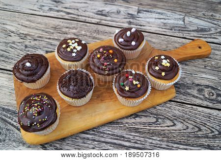 Chocolate Cupcakes. Homemade decorated chocolate cupcakes on natural wood cutting board with rustic background