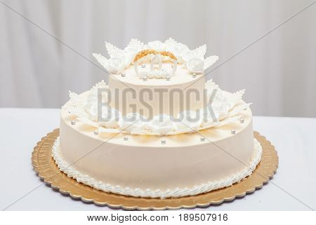 White wedding cake with two gold rings