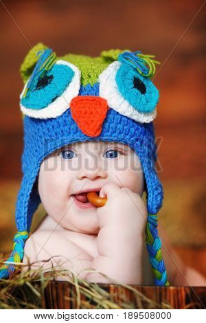 A small boy dressed in a homemade knitted cap in the shape of an owl gnaws a bagel sitting in a hay-filled wooden box