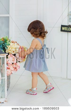 A little girl in a striped dress prepares to meet the groom corrects a huge bouquet of flowers playing house