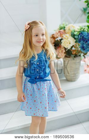 A little girl in a blue shirt and a patterned skirt happily meets her friends at the hen-party standing at the porch of her house