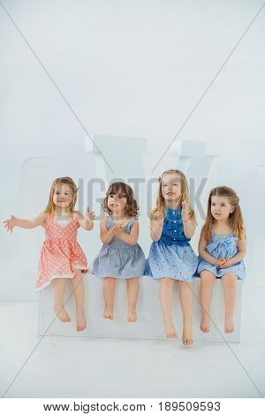 Four girls of fashionable women in beautiful dresses laugh at the hen party sitting on huge white letters on a white background