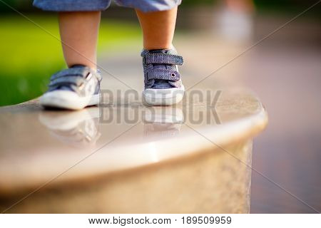 The child's legs in blue sneakers are stepping on the shiny grandiose parapet in the park