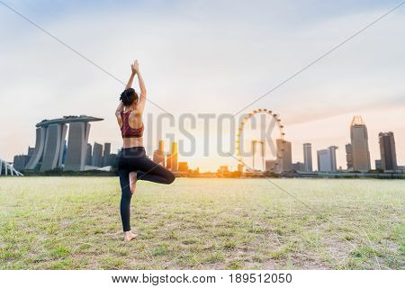Healthy woman doing Yoga exercises on green lawn in sunset time at Marina Bay Sand park singapore city Singapore.