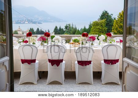 Decorated with red bows and cassets a dining table on the balcony awaits guests. From the balcony you can see the lake at the foot of the Alpine mountains