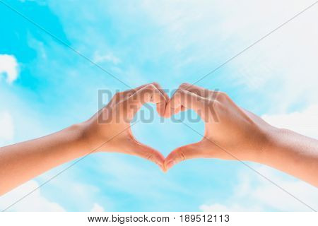 Female hands in the form of heart against the blue sky with cloud. Hands in shape of love heart - Love concept.