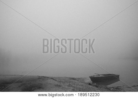 Boat at the shore of the foggy lake