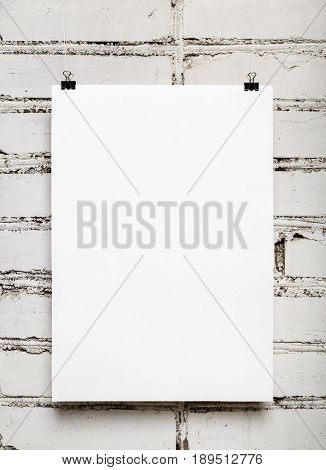 Blank wall calendar with spring on white brick wall background. Template for design calendars and photo albums. Vertical shot.