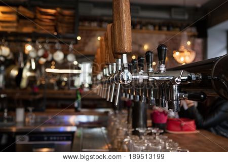 Lot of vintage Golden beer taps in the bar with the bartender in the background
