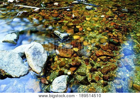 A rocky slow moving stream in fall