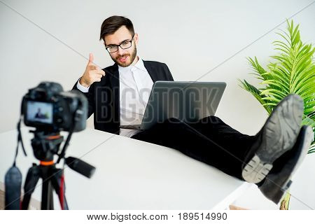 Male blogger recording video at home and winking