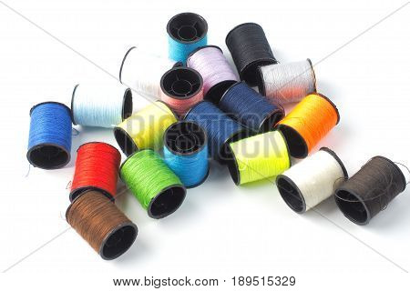 Colorful plastic sewing reels on white background