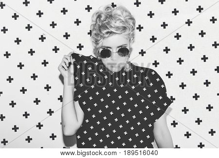 Contrast pattern stylish fashion sexy blonde bad girl in a black t-shirt and rock sunglasses. Dangerous rocky emotional woman. Black and white toned. White background, not isolated