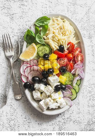 Greek lemon orzo salad. Feta orzo tomatoes cucumbers radishes olives peppers salad on a light background top view. Healthy food concept. Mediterranean food style