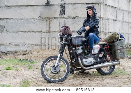 A post apocalyptic woman on motorcycle near destroyed building