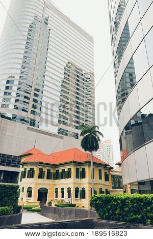 W Hotel in Bangkok, Thailand. May, 30 2017. View of hotel by street. Yellow vintage style Building between two skyscrapers on North Sathorn Road