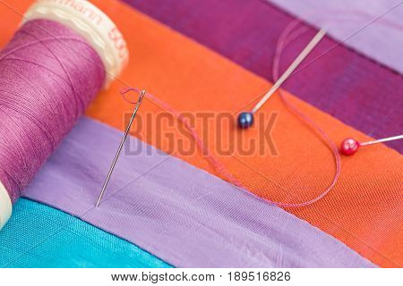 quilting, sewing, tailoring and fashion concept - macro of spool of threads, needle and pins, beautiful colored patchwork fabrics, colorful stitched textile scraps at workshop, top view.