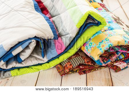 patchwork and fashion concept - close-up on beautiful colorful quilts folded on a whitewashed wooden floor, close-up on patchwork products on a white background, top view, vertical