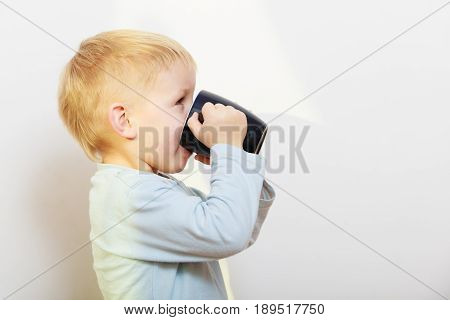 Good daily human hydration concept. Thirsty kid boy drinking drink from black mug