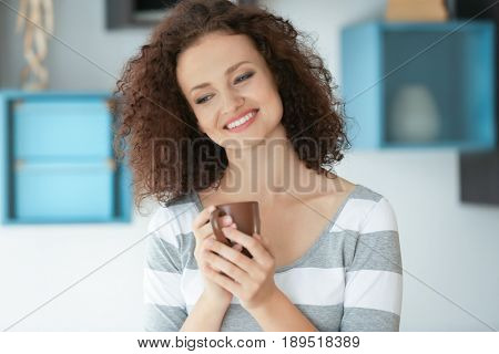 Young woman with cup of aromatic coffee in the room
