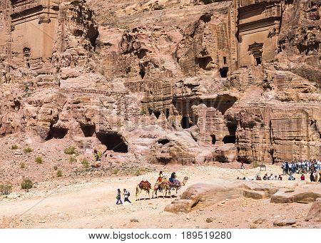 Petra Jordan - 9 March 2017: Tourists walking through the rock tombs Petra Jordan 9 March 2017