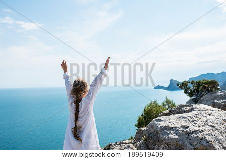 Small girl stay on the top of mountain looking on the beautiful view blue sea and mountains. Summer concept. Travel to Crimea Sudak