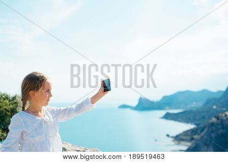 Small girl takes picture on smartphone looking on beautiful view blue sea and mountains. Summer concept. Travel to Crimea Sudak
