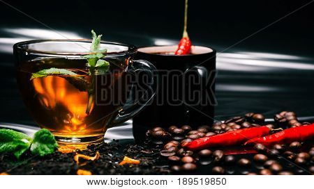 Black tea in transparent cup with fresh mint and coffee in black cup with red chili peppers on glossy black background covered with dried black tea and roasted coffee beans. Selective focus