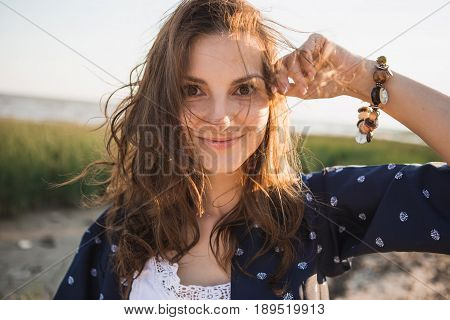 Woman 30-40 years dressed in boho style holding herself by the head