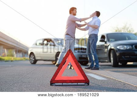 Two angry men arguing after a car fender-bender crash
