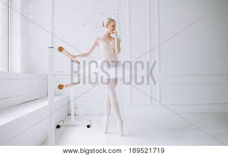 Young bautiful ballerina in tutu standing on pointes at barre in ballet class. She is biting her fingers because girl is worrying before the great perfomance