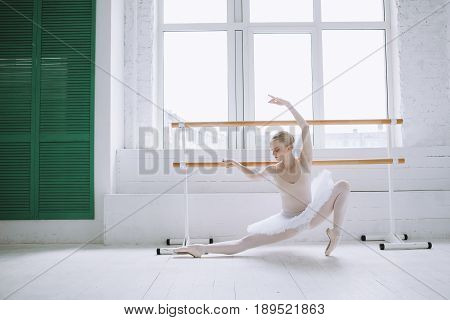 The classic ballet dancer posing at ballet barre on a rehearsal room or she is doing some stretching and main position or moves in the ballet.