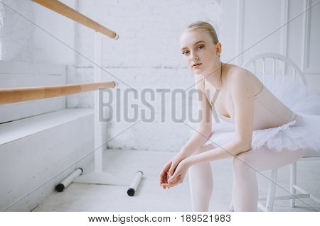 Young weary ballerina but with a great pleasure on her face relaxing after big work. She is looking at the camera with tired and satisfied face expression. Close up
