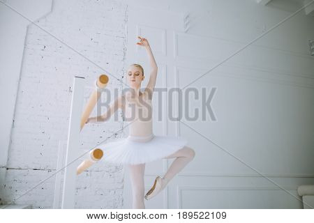 Young concentrated ballerina with look down standing on pointes at barre in ballt class and doing steps. She is practicing in ther rehearsal room